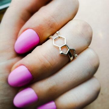 pierścionek z wzorem serotoniny na dłoni z pomalowanymi na różowo paznokciami