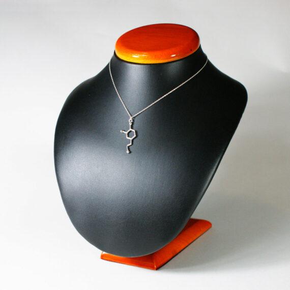 srebrny naszyjnik z zawieszką z wzorem chemicznym dopaminy na ekspozytorze