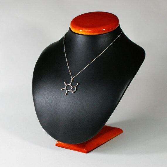 srebrny łańcuszek z zaiweszką z wzorem chemicznym kofeiny na ekspozytorze
