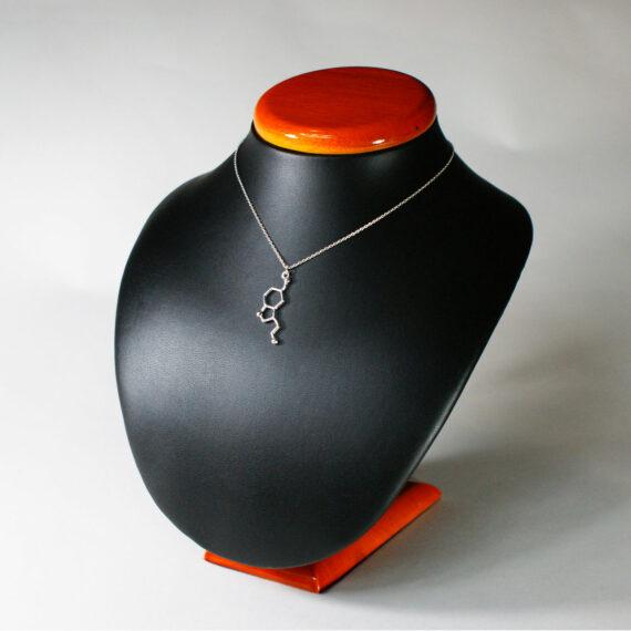 srebrny naszyjnik z zawieszką z wzorem chemicznym serotoniny na ekspozytorze