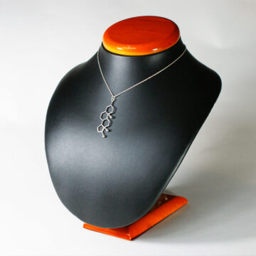 srebrny naszyjnik z zawieszką z wzorem chemicznym testosteronu na ekspozytorze
