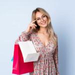 młoda kobieta w okularach trzymająca torby prezentowe
