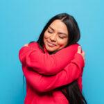 młoda kobieta w czerwonej bluzie obejmująca siebie na bienieskim tle