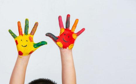 pomalowane kolorywmi farbami dłoinie z namalowanymi uśmiechami