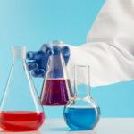 ręka chemika w fartuchu i rękawiczce stawiająca na stole zlewkę z substancją chemiczną